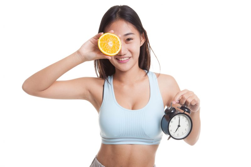 Beautiful Asian healthy girl with orange and clock isolated on white background.