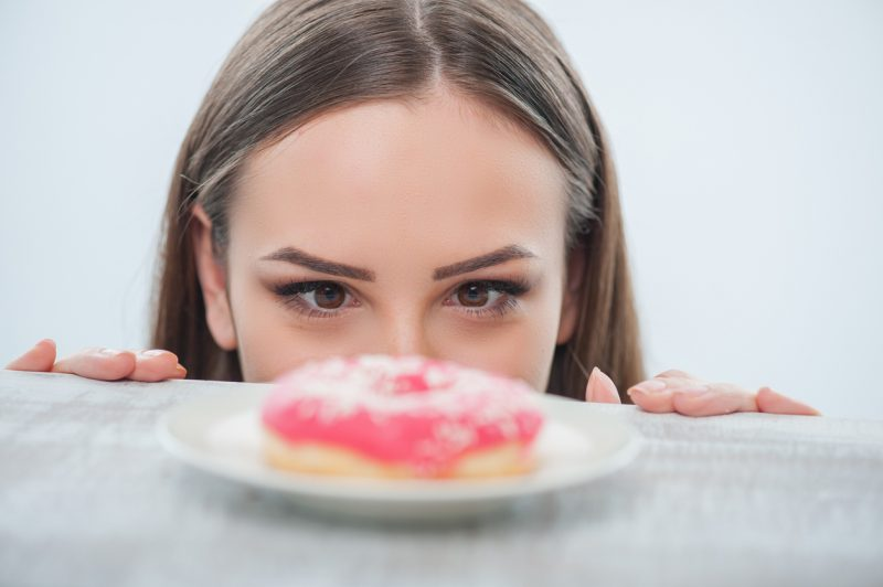 Beautiful girl is looking at unhealthy donut with appetite. It is situated on a table. Isolated on a white background