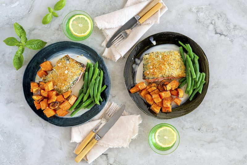 A top down food photography shot of a crumbed fish and green beans dish.